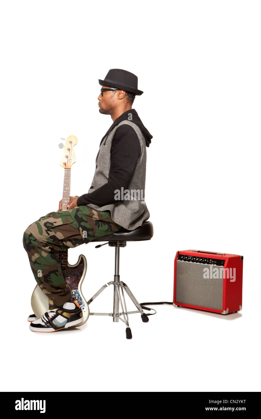 Man sitting on stool with electric guitar - Stock Image