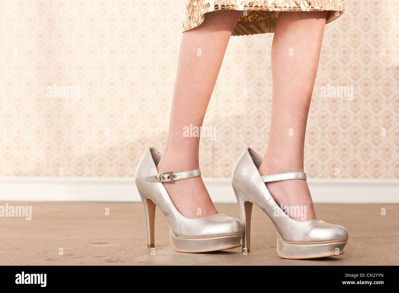 Girl wearing her mother's high heels - Stock Image