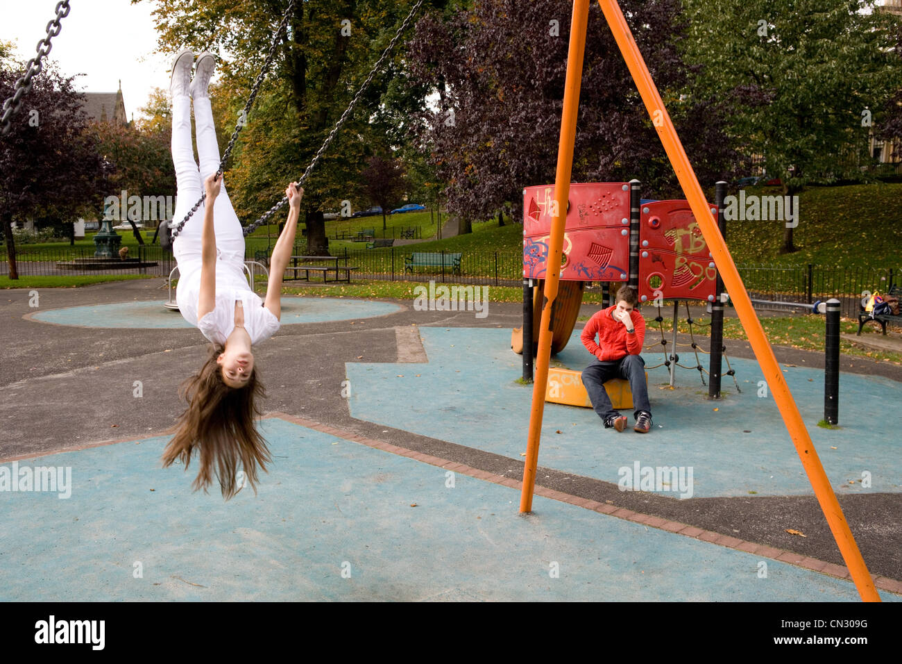 Teenage girl on swing in playground, upside down - Stock Image