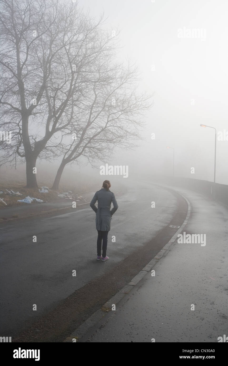 Teenage girl standing in road in the mist - Stock Image