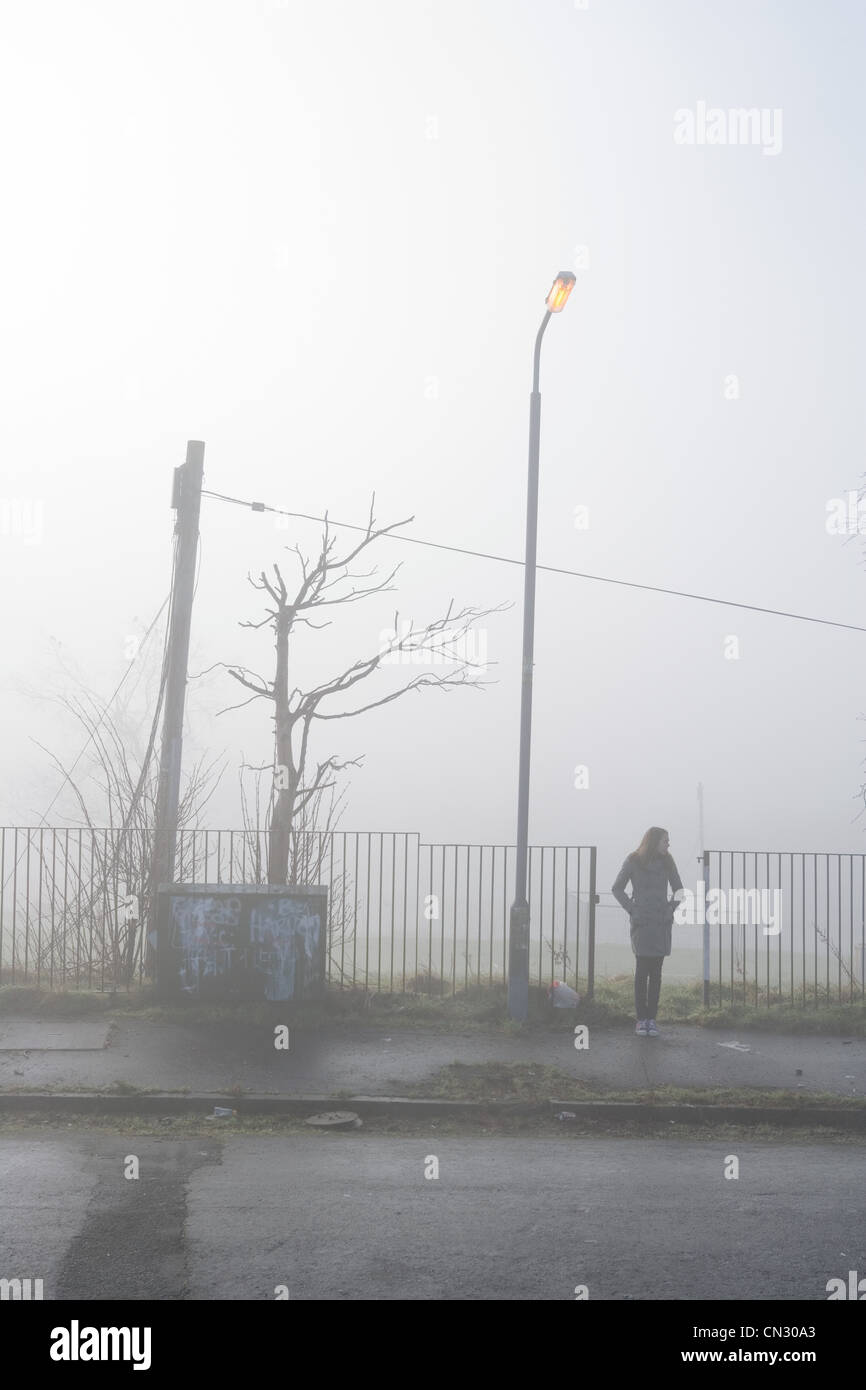 Teenage girl standing on pavement in the mist - Stock Image