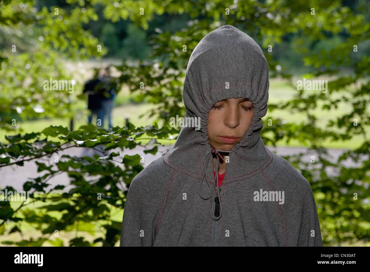 Teenage girl wearing grey hooded top - Stock Image