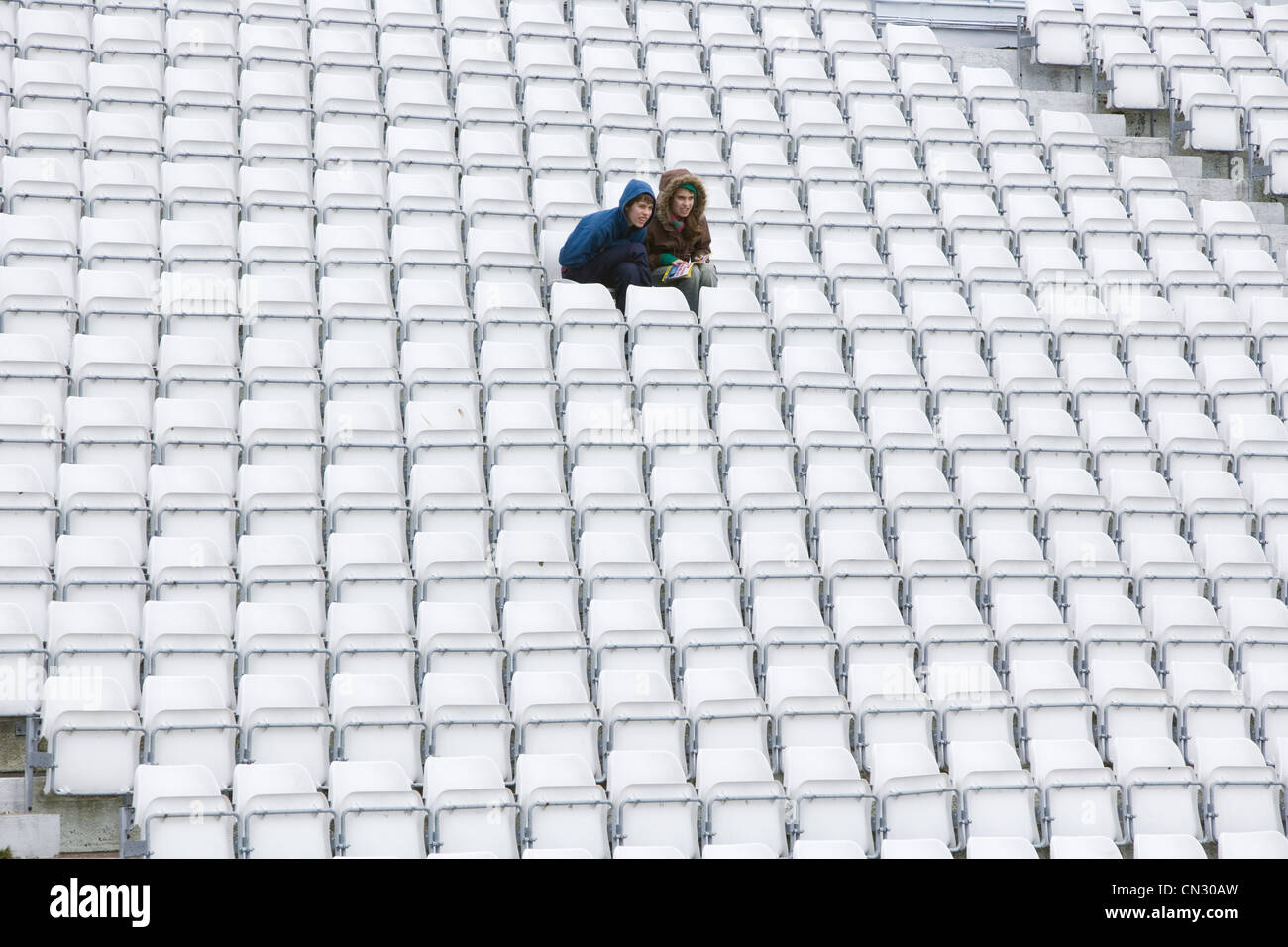 Couple sitting on stadium seats - Stock Image