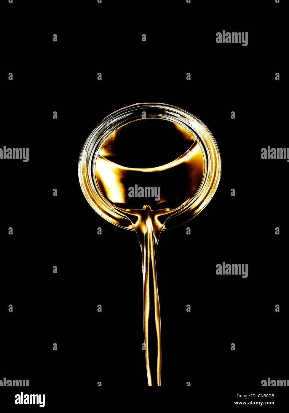 Pouring gold liquid - Stock Image