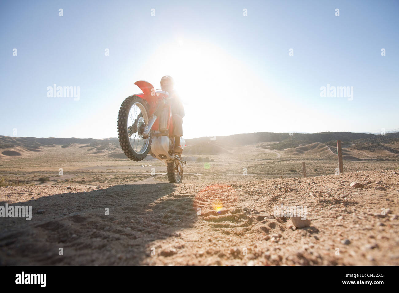 Man doing wheelie on dirt bike on dirt track - Stock Image