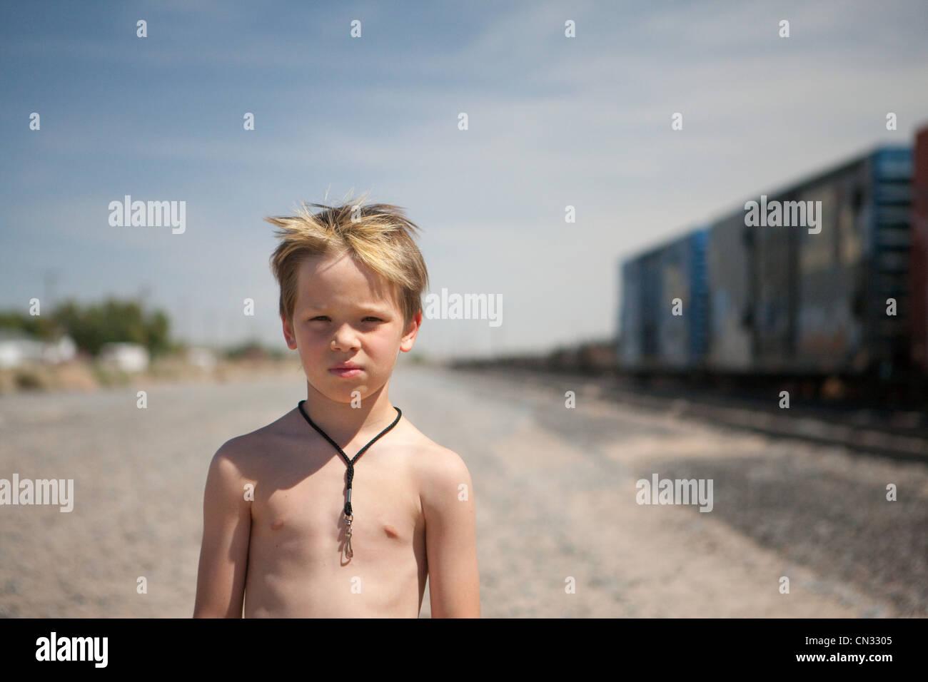 Boy by train tracks - Stock Image