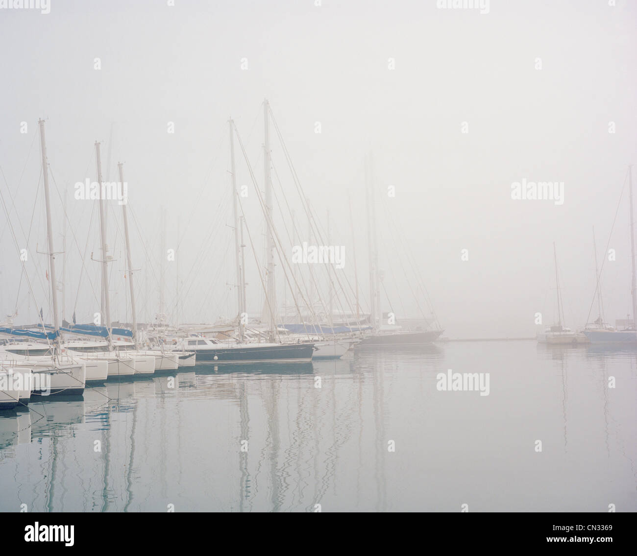 Boats in harbour in fog Stock Photo