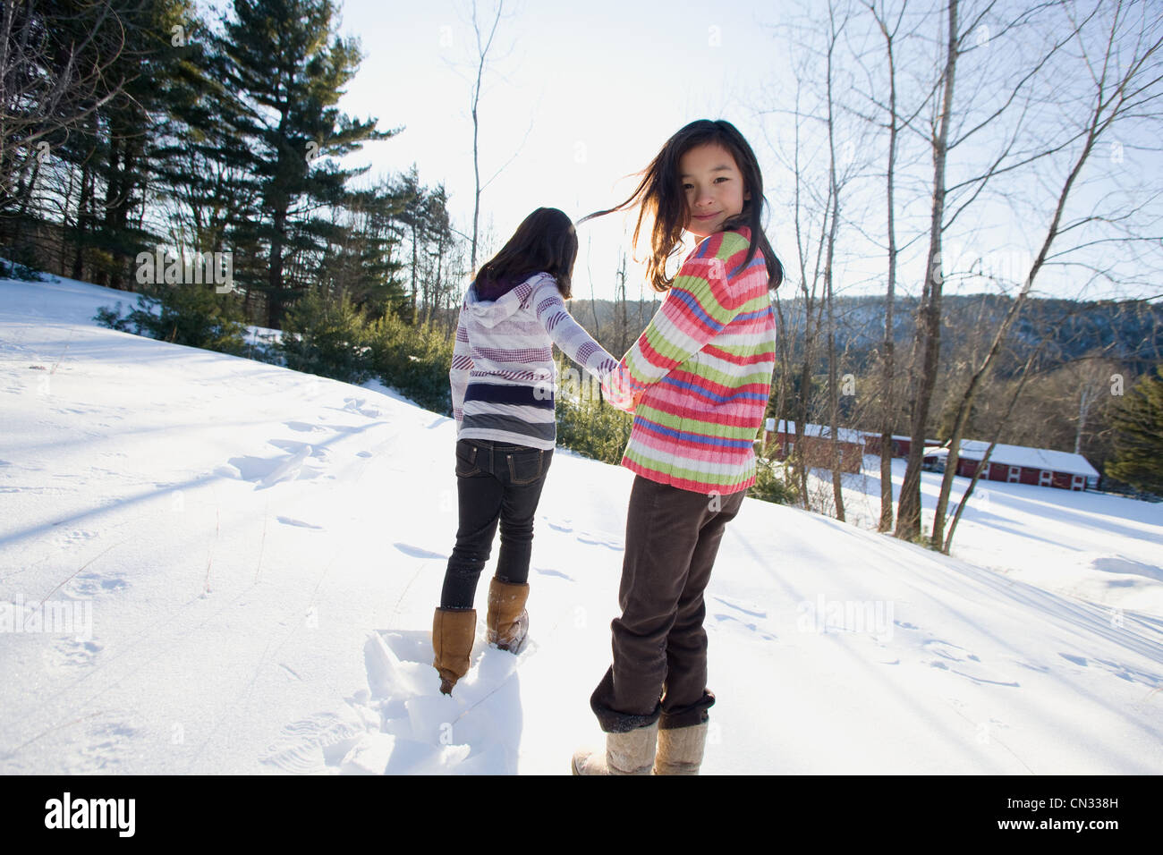 Two girls walking in the snow - Stock Image