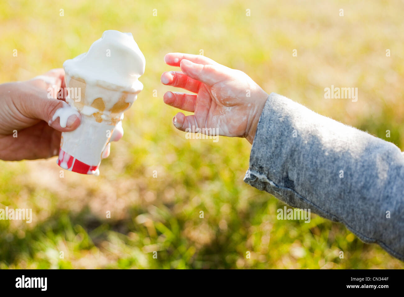 Toddler taking ice cream cone - Stock Image