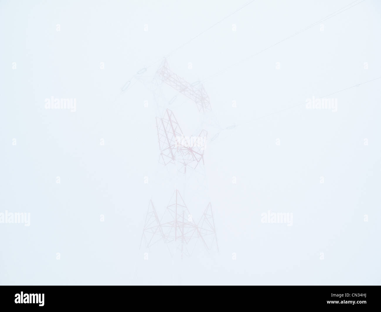Electricity pylon in dense cloud,Grand Massif, French Alps - Stock Image