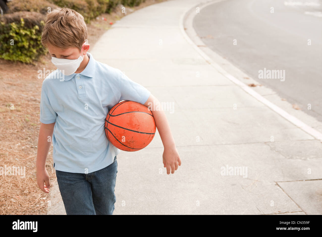Boy wearing dust mask holding basketball Stock Photo