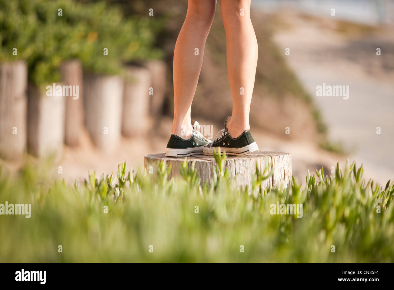 Young woman walking on wooden post - Stock Image