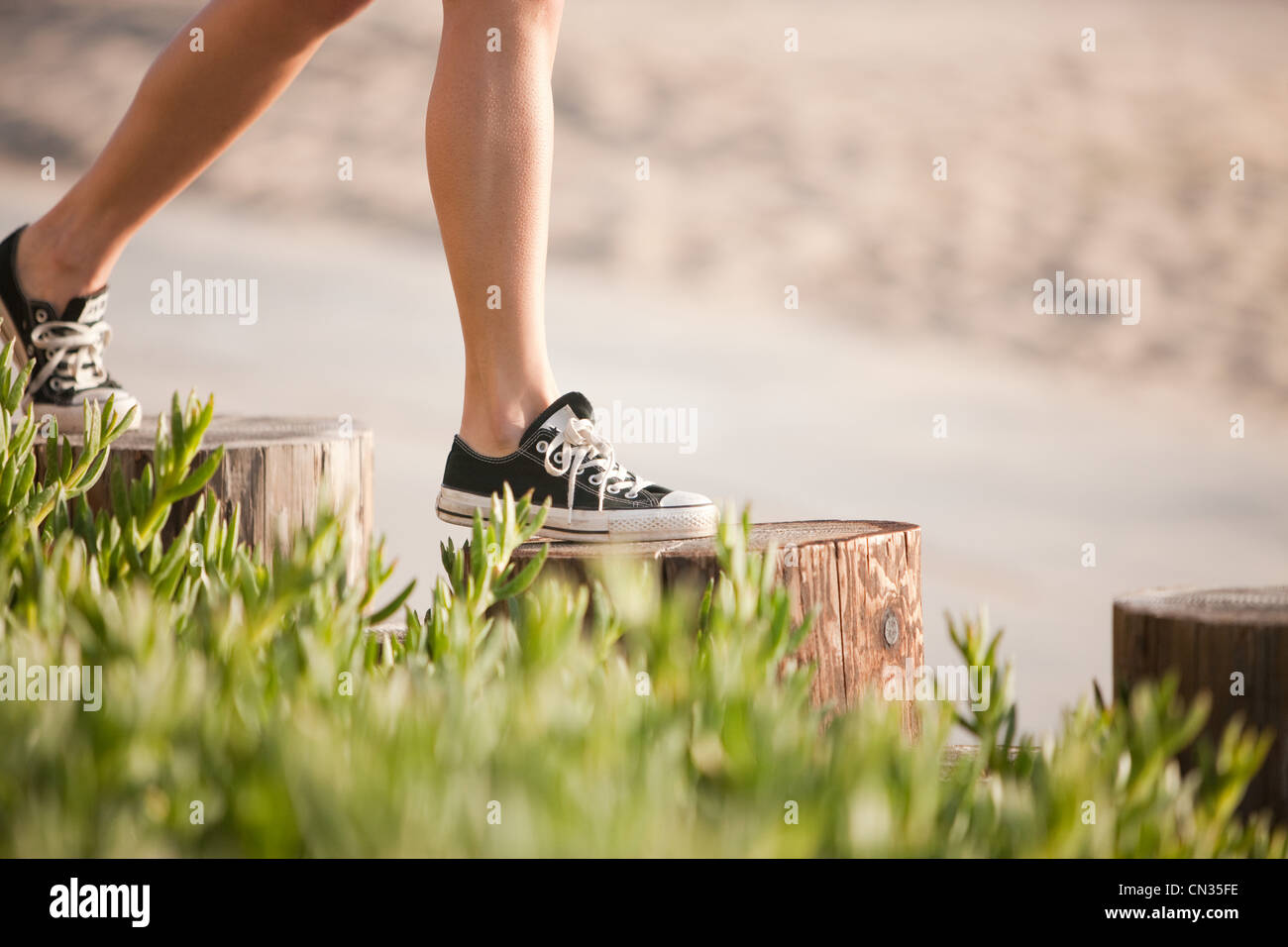 Young woman walking on wooden posts - Stock Image