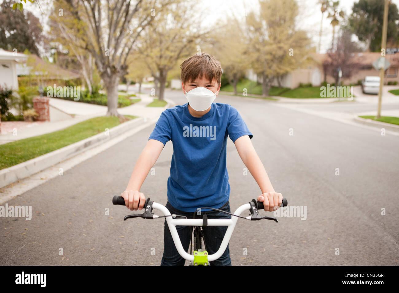 Boy on bicycle wearing dust mask - Stock Image