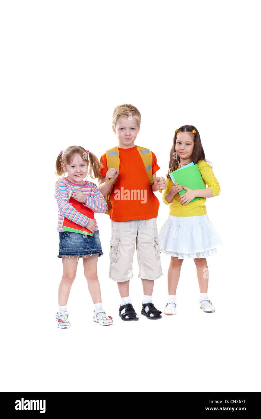 Three school children isolated on white background looking confidently at camera - Stock Image