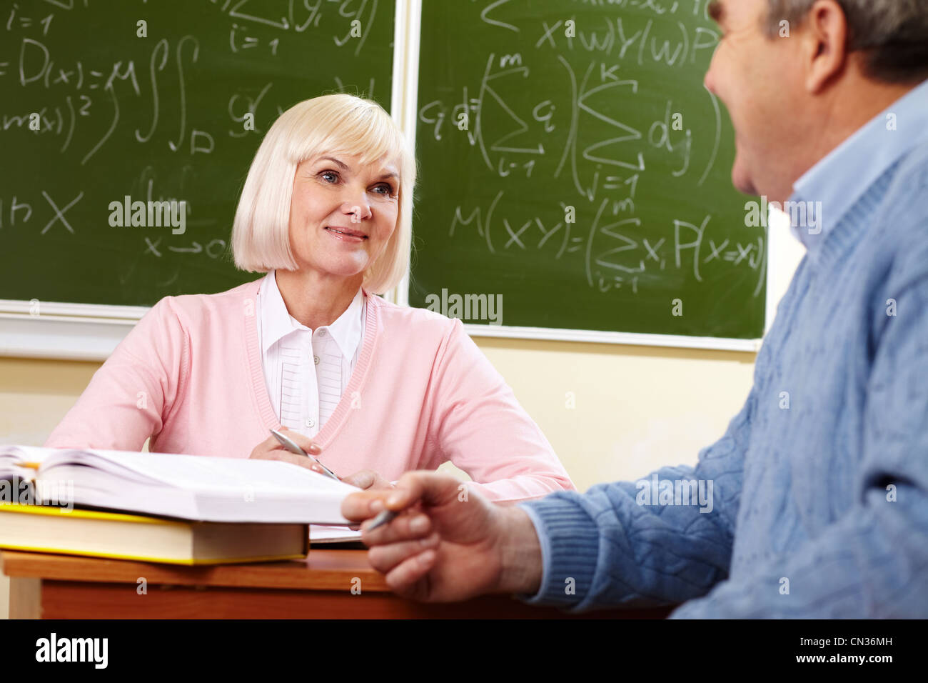 Elderly people looking at each other with a smile during the break between lessons - Stock Image
