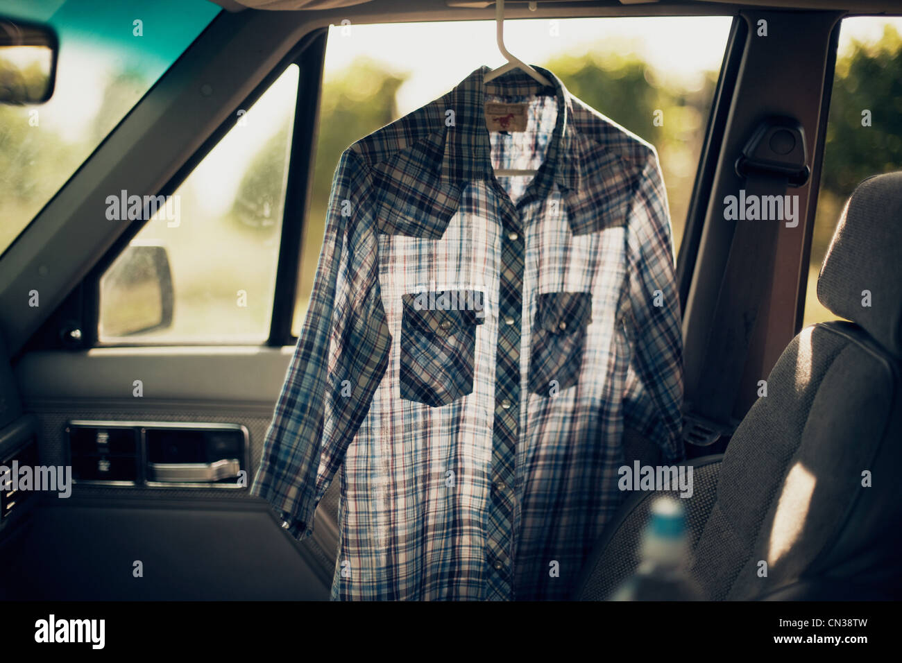 Checkered shirt in a car - Stock Image