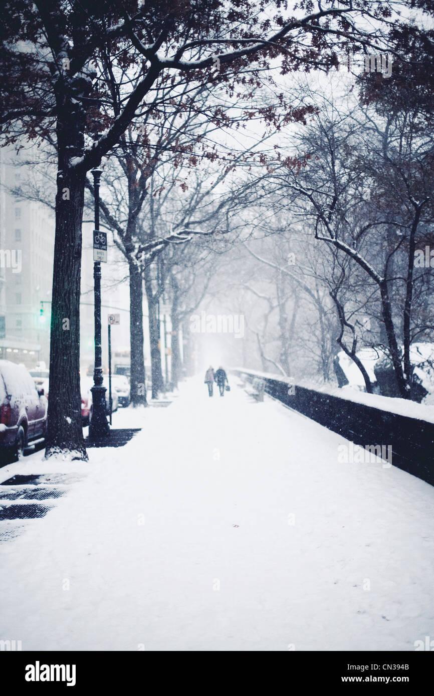 People walking in snow on street - Stock Image