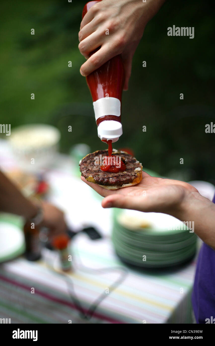 Person squeezing ketchup onto burger - Stock Image