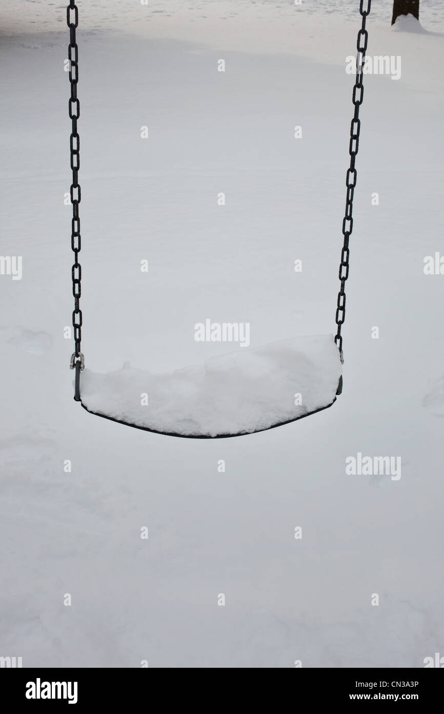 Snow covered swing - Stock Image