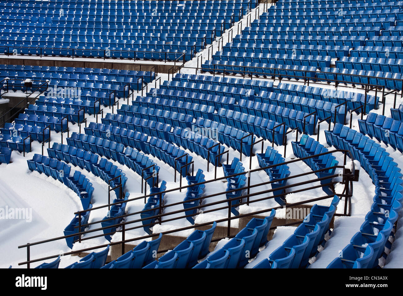Empty stadium seats in the snow - Stock Image
