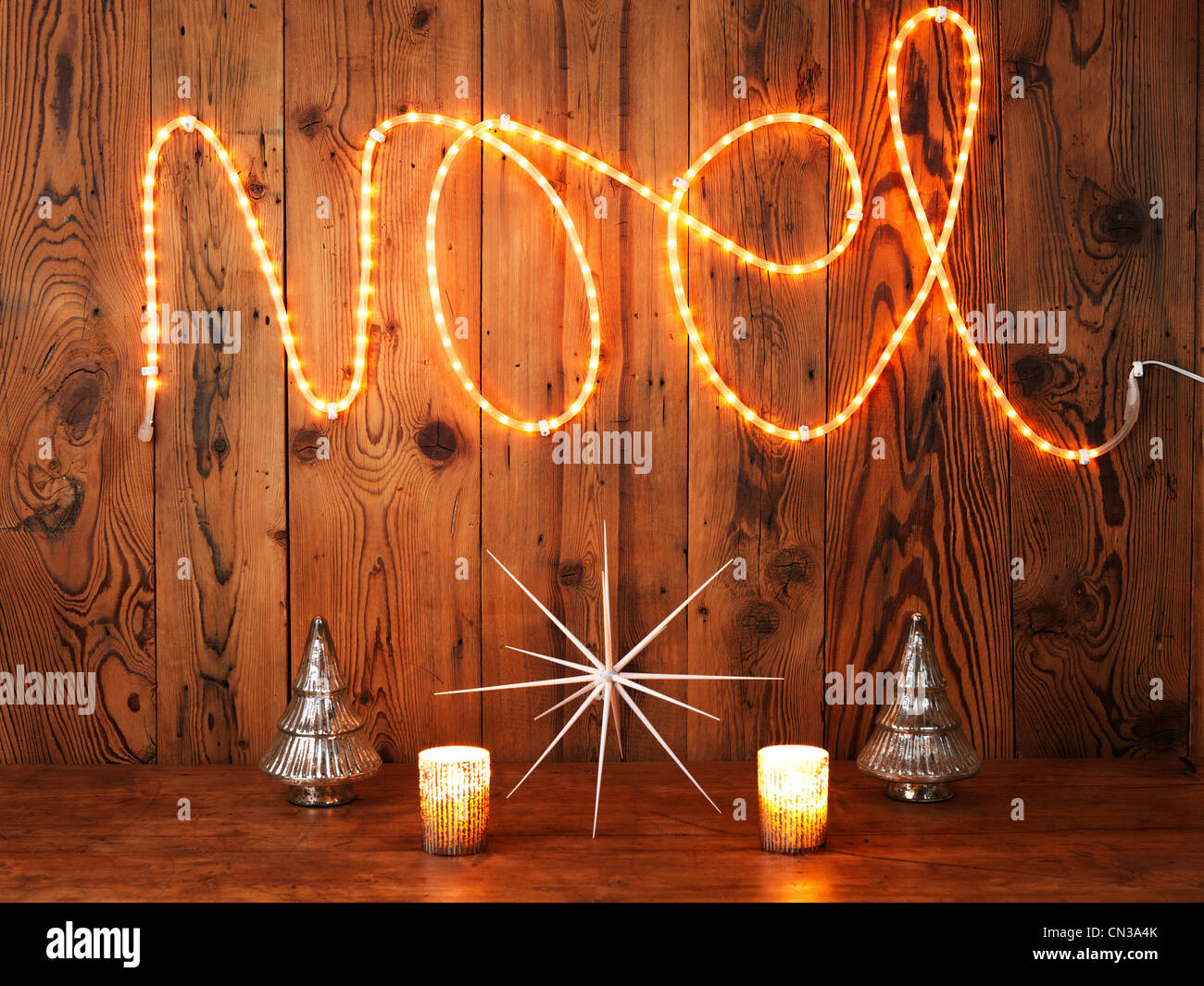 Christmas lights spelling Noel against wood panelling - Stock Image