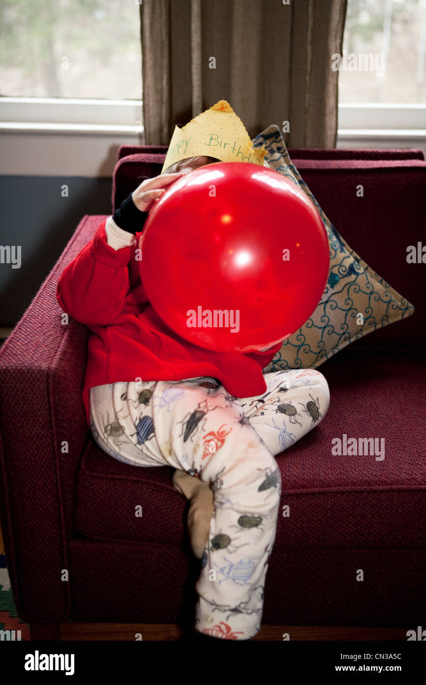 Boy blowing up red birthday balloon - Stock Image