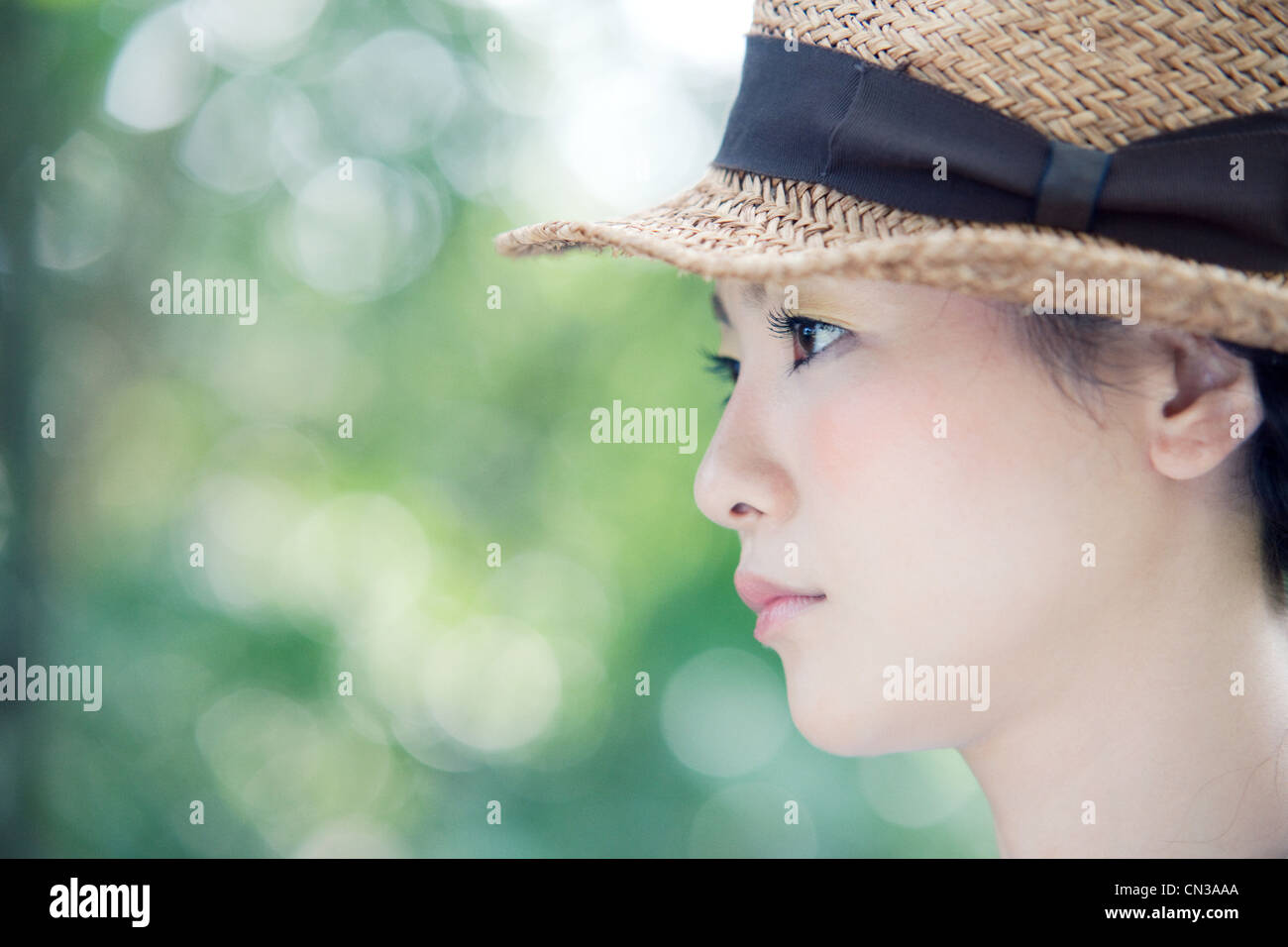 Young woman wearing straw hat, portrait - Stock Image
