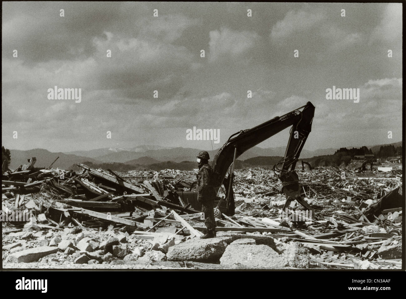 Rikuzentakata, Japan- 20th March 2011: Soldier amongst debris in aftermath of the 2011 Tohoku Earthquake and Tsunami - Stock Image