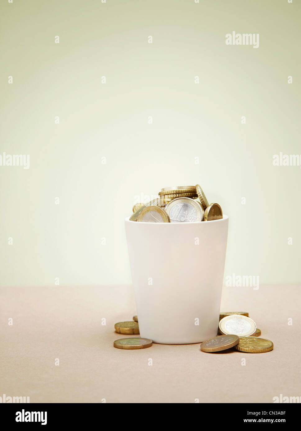 Plant pot full of euro coins - Stock Image