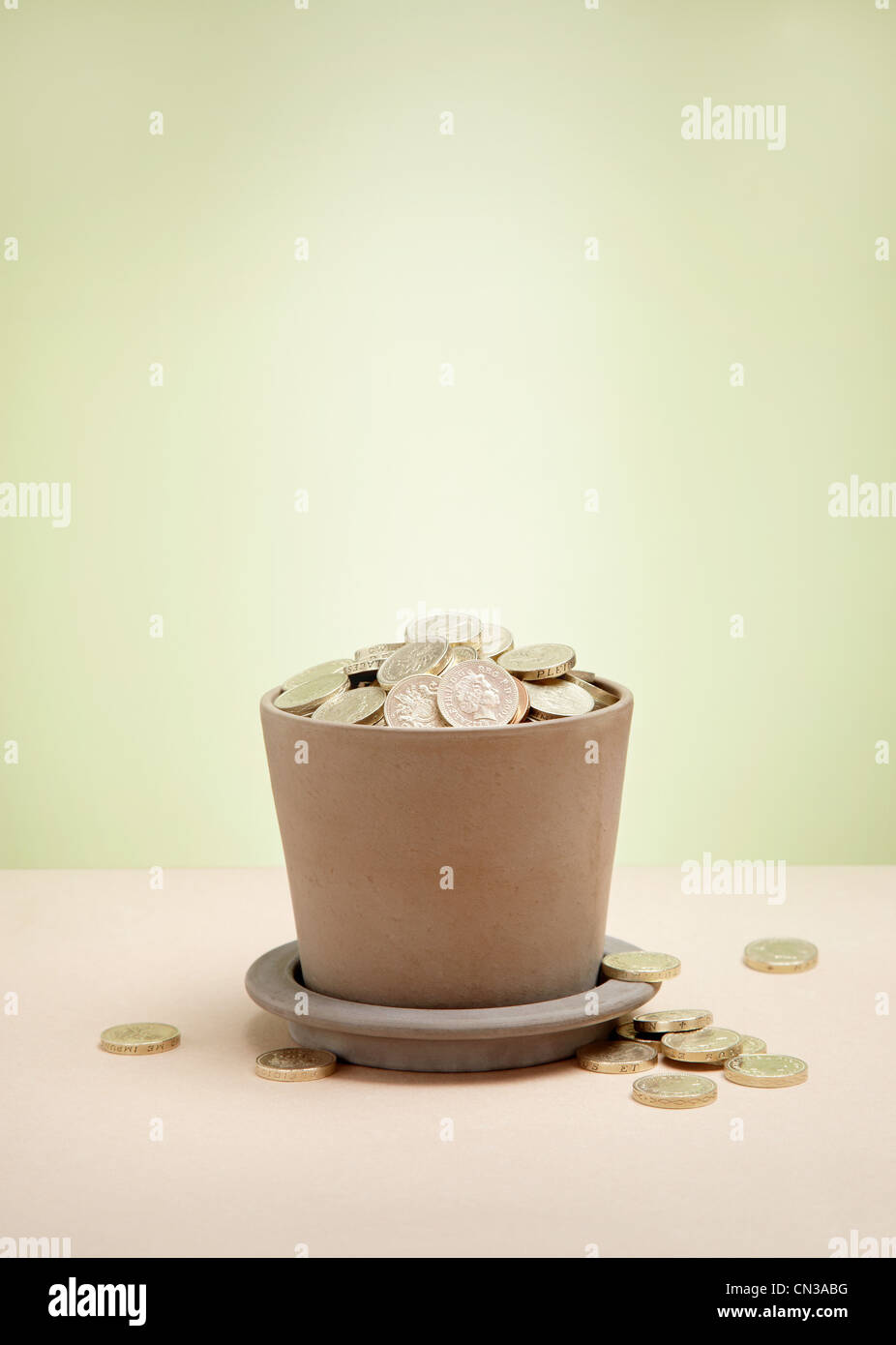 Plant pot full of pound coins - Stock Image