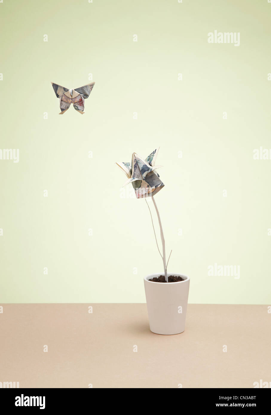 Origami butterfly and yen banknote in plant pot - Stock Image