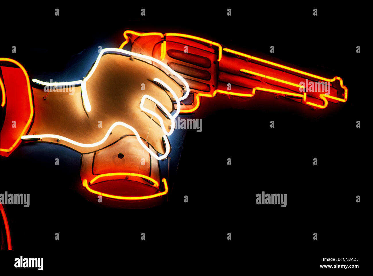 Neon sign of hand holding gun - Stock Image