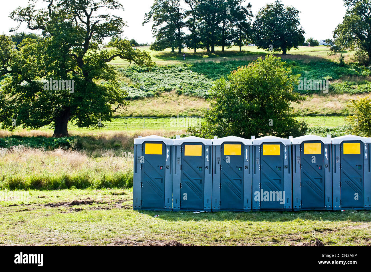 Row of portable toilets in field - Stock Image