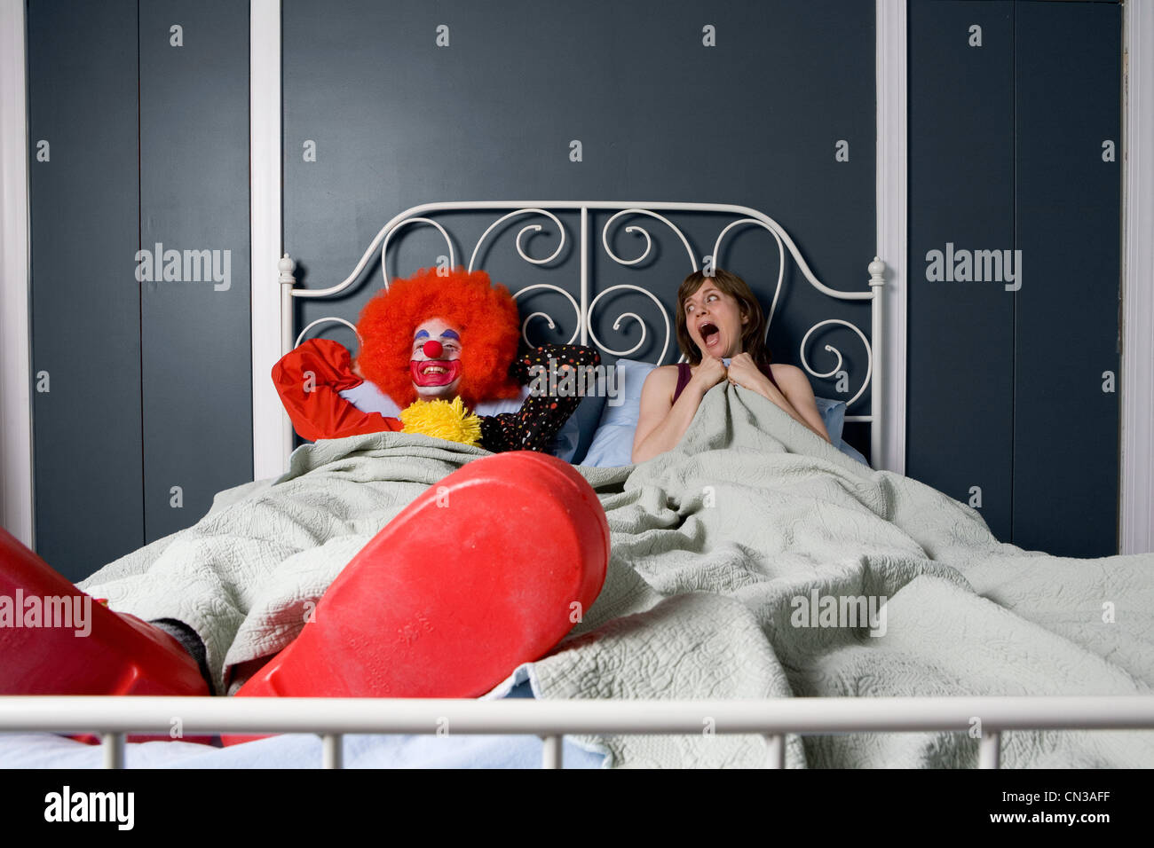 Woman screaming as she realises she is in bed with a clown - Stock Image