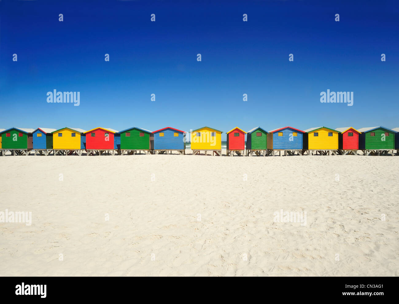 Brightly colored beach huts on beach - Stock Image