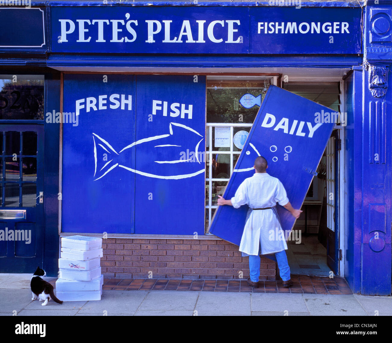 Fishmonger putting up shop front signs - Stock Image
