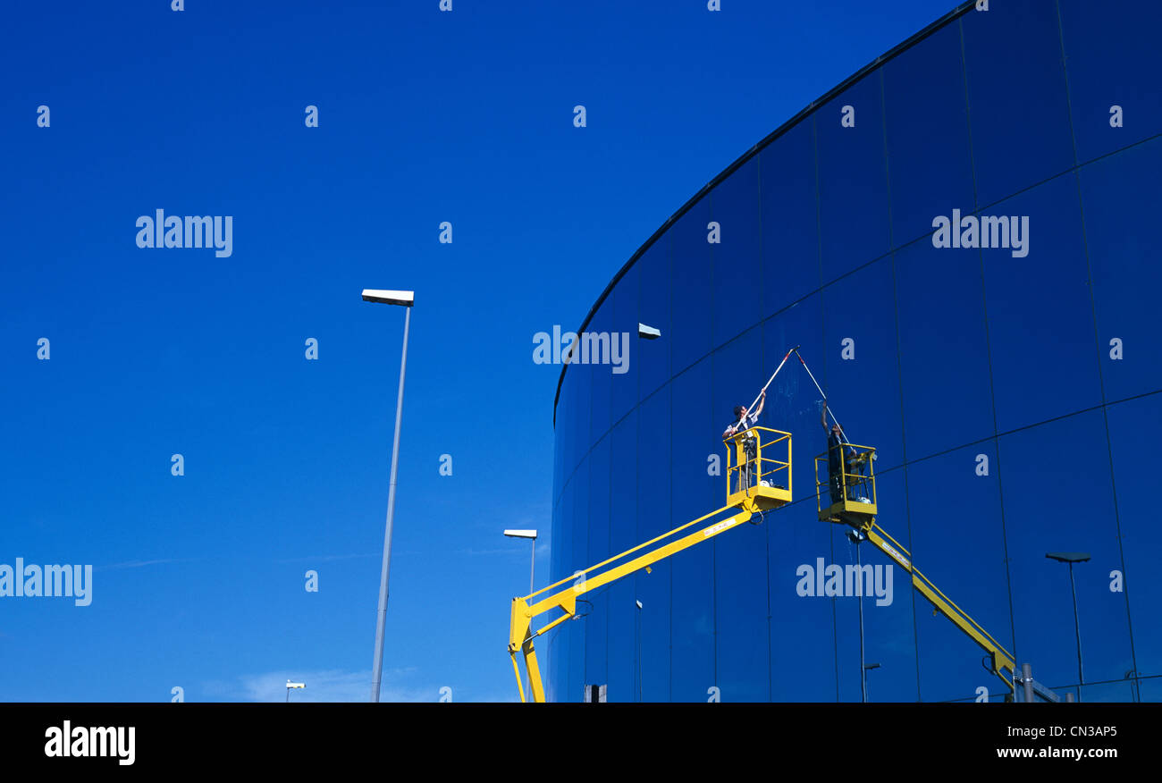 Person in access platform cleaning office window - Stock Image