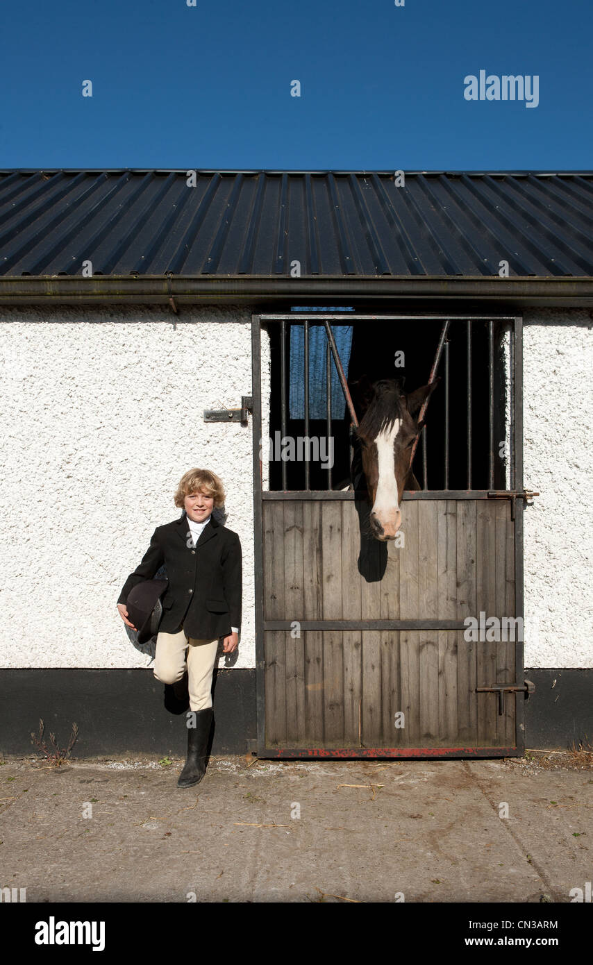 Boy standing by horse stables - Stock Image