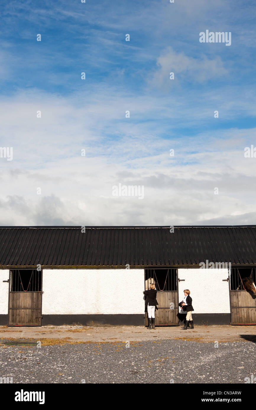 Boys standing by stables Stock Photo