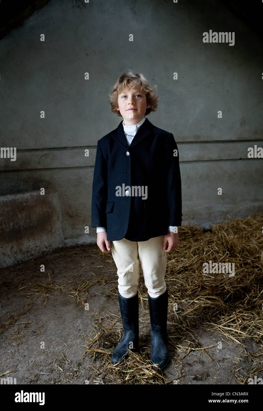 Boy Standing In Horse Riding Clothes In Stable Stock Photo Alamy
