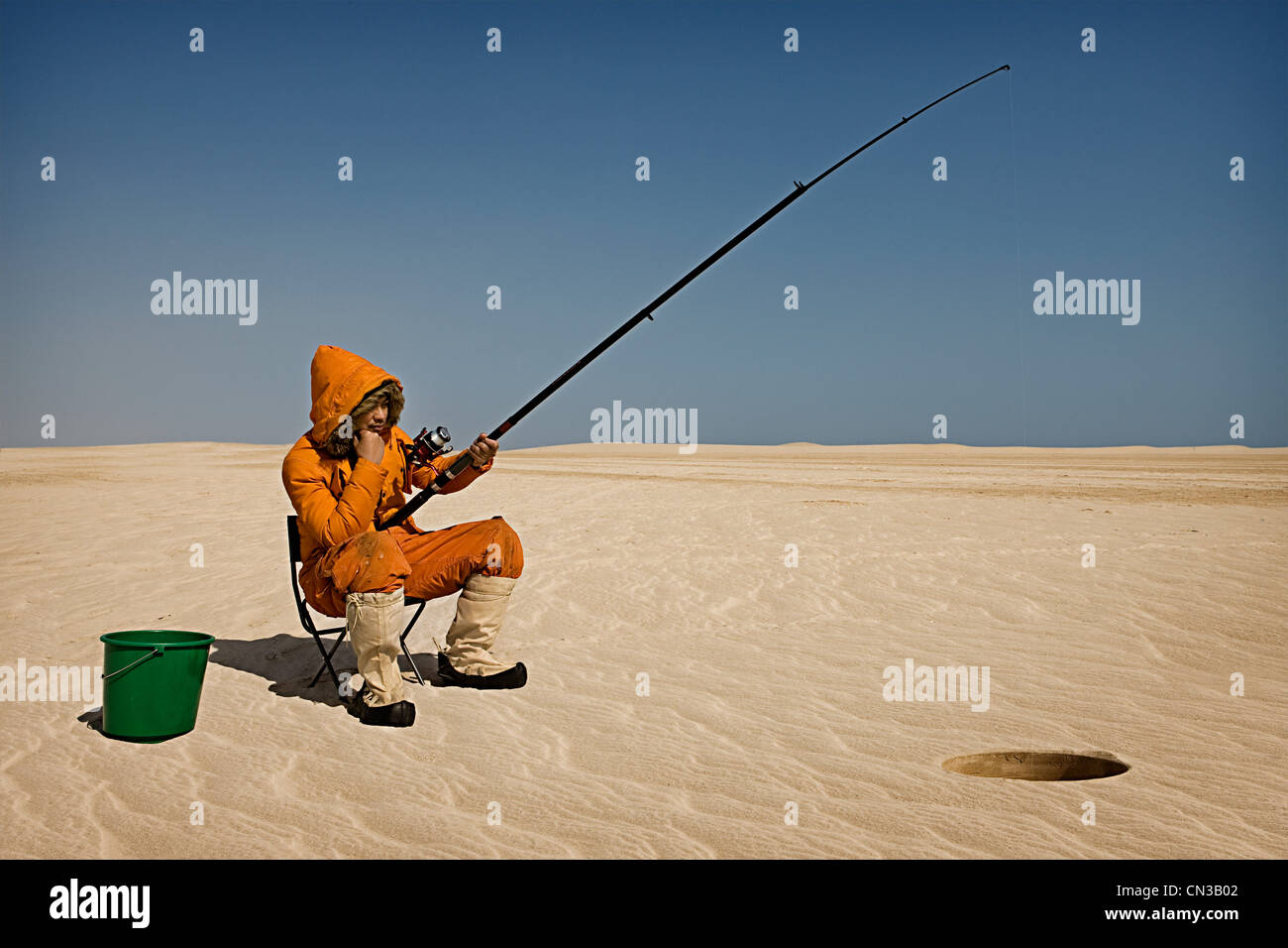 Eskimo fishing in desert Stock Photo