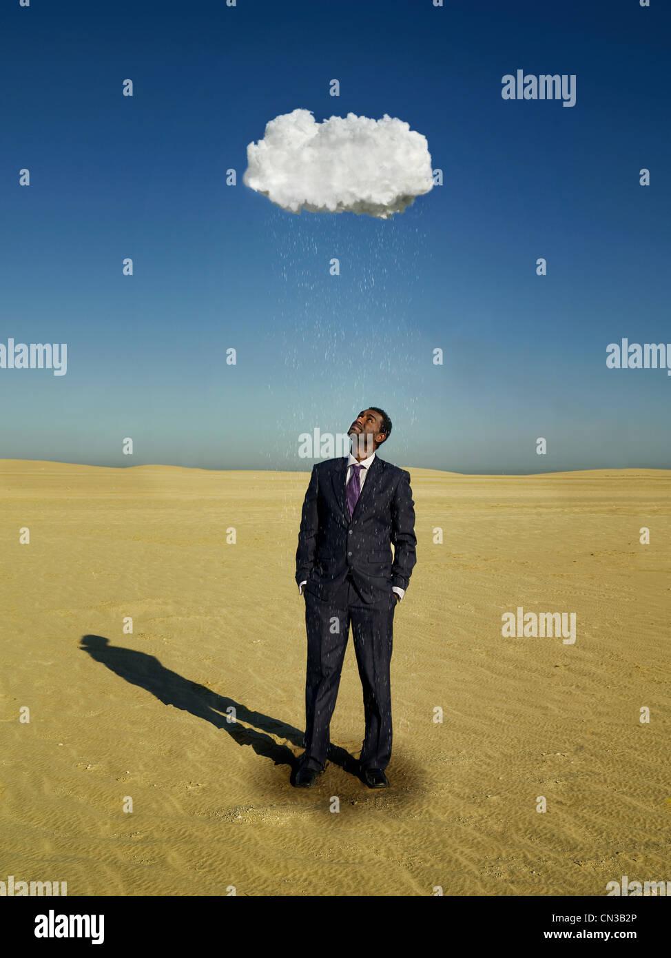 Businessman standing under raincloud in desert - Stock Image