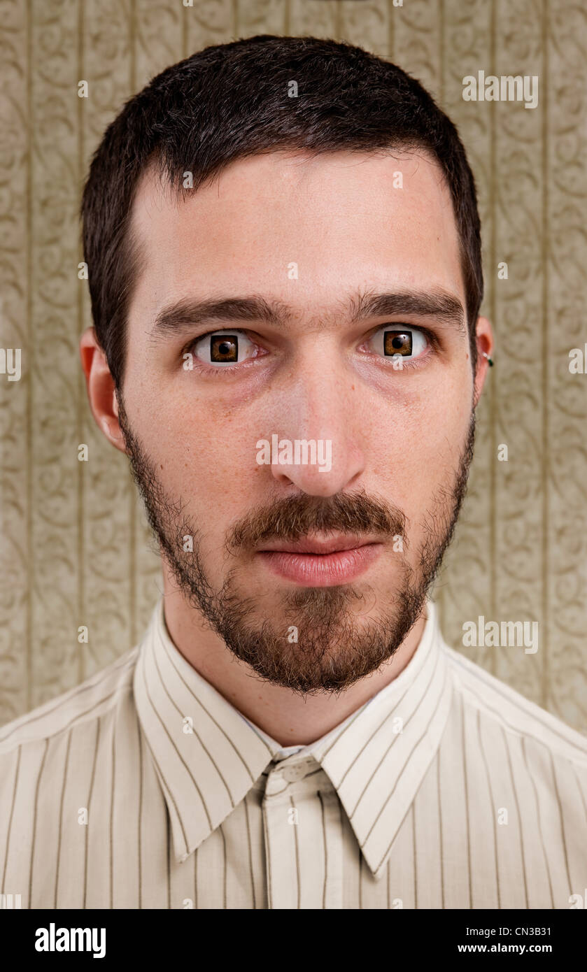 Portrait of mid adult man with square eyes - Stock Image
