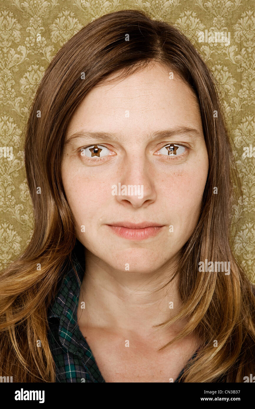 Portrait of mid adult woman with star shaped eyes - Stock Image