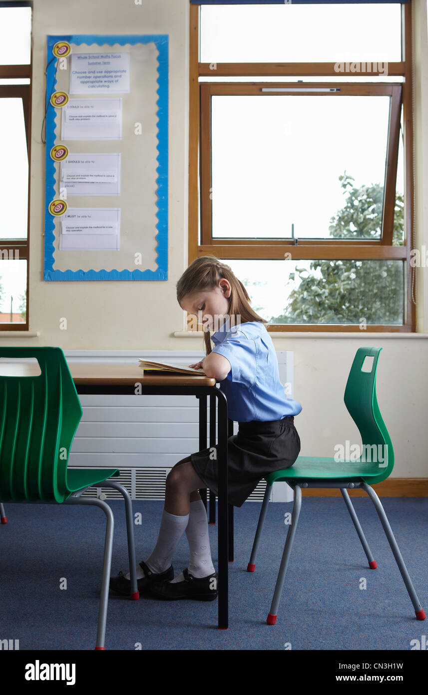 School girl reading a book at a desk in a classroom - Stock Image