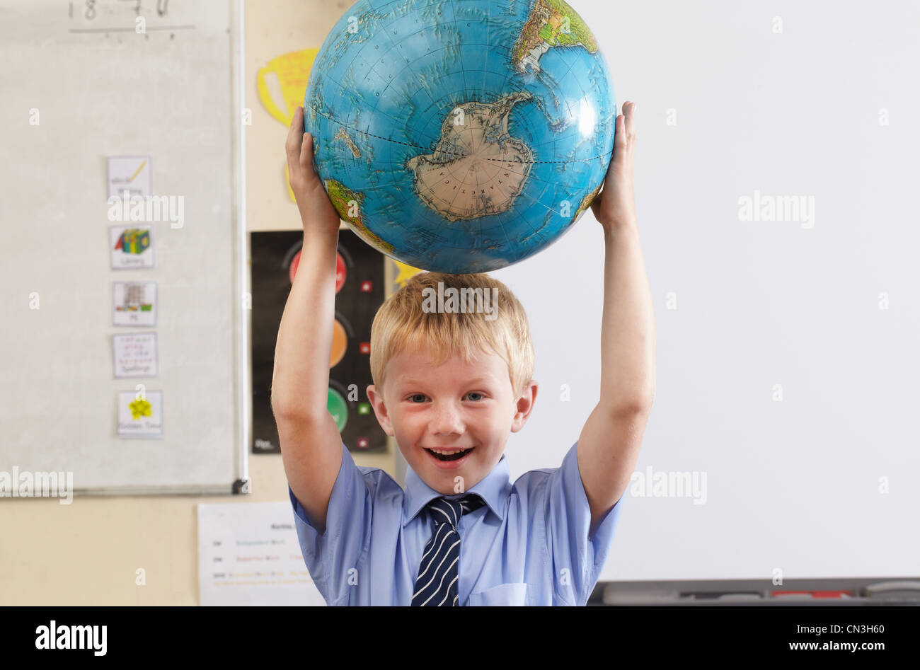 School boy holding globe over his head in a classroom - Stock Image