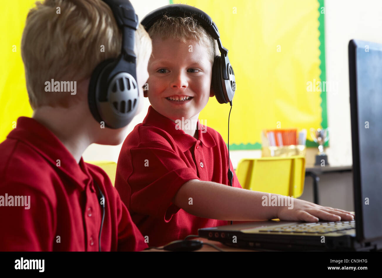 School boys wearing headphones and looking at computer in classroom Stock Photo