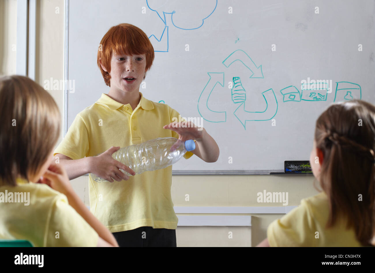 School children discussing recycling issues in classroom - Stock Image