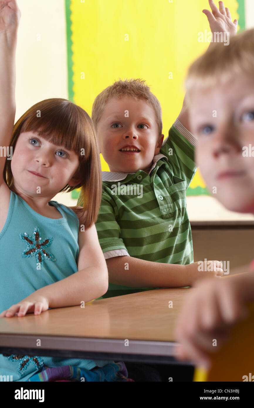 School children answering a question in the classroom - Stock Image
